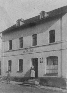 """Margarethe Merz im Jahr 1930 vor dem Eingang zur früheren Gaststätte """"Zur Linde""""."""